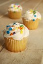 Cupcakes colorful sprinkles wooden table Stock Photos