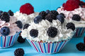 CUPCAKES WITH CREAM AND BERRIES BLACKBERRY, BLUEBERRY Royalty Free Stock Photo