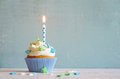 Cupcakes with cream and sugar butterflys and birthday candle Royalty Free Stock Photo