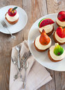 Cupcakes with vanilla buttercream and marzipan fruits on wooden background Royalty Free Stock Images