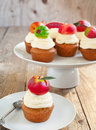Cupcakes with vanilla buttercream and marzipan fruits on wooden background Stock Image