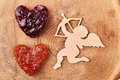 Cupid near heart-shaped jelly bread. Royalty Free Stock Photo