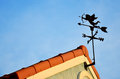 Cupid weathercock atop roof in clear blue sky Stock Photos