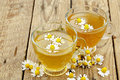 Cups of chamomile tea with flowers on wood Stock Photos