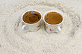 Cups with coffee stand on sand Royalty Free Stock Photo
