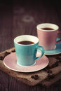 Cups of espresso on a wooden table two with coffee beans dark background selective focus Stock Photos