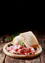 Cured ham with crusty rolls for a country lunch thinly sliced german served on wooden platter copyspace vertical format Stock Images