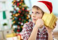 Curiosity portrait of pensive boy holding giftbox and guessing what is inside on christmas evening Stock Photos