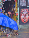 Curiosity shop owner sitting inside his and looking on passing toursits near the swayambhu stupa kathmandu nepal Stock Images