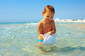 Curious baby boy catches jellyfish in the sea Royalty Free Stock Photography