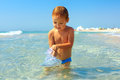 Curious baby boy catches jellyfish in the sea Stock Photography