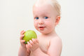 Curious blond baby eating apple closeup portrait of a with blue eyes on a light background Stock Images