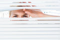 Curious blonde woman looking through venetian blind on a sunny day Royalty Free Stock Image