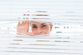 Curious blonde woman looking through venetian blind on a sunny day Royalty Free Stock Images