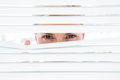 Curious blonde woman looking through venetian blind on a sunny day Royalty Free Stock Photos