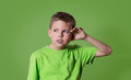 Curious boy listens. Closeup portrait child hearing something, parents talk, gossips, hand to ear gesture isolated on green. Royalty Free Stock Photo