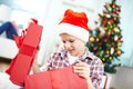 Curious boy portrait of looking inside big red giftbox on christmas evening Stock Photography