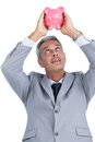 Curious businessman holding piggy bank above his head on white background Stock Photography