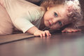 Curious cute child hiding under the bed in kids room and looking scared Royalty Free Stock Photo