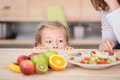 Curious girl looking at fruit salad in kitchen little cropped mother prepare the Royalty Free Stock Photos