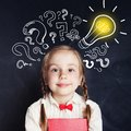 Curious kid of school age with lightbulb and chalk question mark Royalty Free Stock Photo