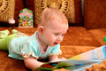 Curious little baby book sofa Royalty Free Stock Image