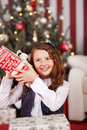 Curious little girl shaking her christmas gift pretty trying to guess the contents Stock Photos