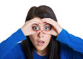 Curious man closeup portrait of young funny woman looking through fingers like binoculars searching for something surprised Royalty Free Stock Image