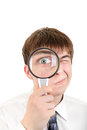 Curious teenager with a loupe portrait of on the white background Royalty Free Stock Photos