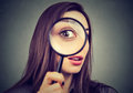 Curious woman looking through a magnifying glass Royalty Free Stock Photo
