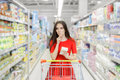 Curious woman in the supermarket with shopping list young girl a market store a thinking what to buy Royalty Free Stock Photography
