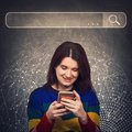 Curious woman using smartphone browsing network search bar with loupe to find useful information and data. Internet searching