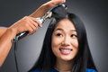 Curling procedure close up image of a cheerful young woman having in the salon over grey Stock Photos