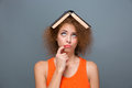 Curly annoyed woman looking funny with book on head Royalty Free Stock Photo
