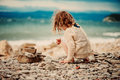 Curly child girl building stone tower on the beach Royalty Free Stock Photo