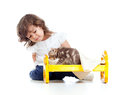 Curly child girl playing with kitten Royalty Free Stock Photos