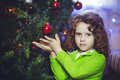 Curly girl near the christmas tree little Royalty Free Stock Photos