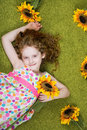 Curly girl with sunflower in grass carpet. Royalty Free Stock Photo