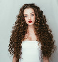 Curly hair woman portrait long hair with perfect make up red lips. Royalty Free Stock Photo