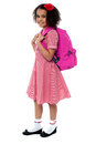 Curly haired elementary school girl in uniform carrying pink backpack on shoulders Stock Photography