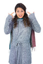 Curly haired model with winter clothes pointing out her head on white background Stock Photography