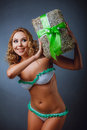 Curly-headed girl in bikini with gift Royalty Free Stock Photo