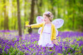 Curly toddler girl in fairy costume in bluebell forest Royalty Free Stock Photo