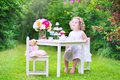 Curly toddler girl playing tea party with a doll adorable hair wearing colorful dress on her birthday teddy bear toy dishes Royalty Free Stock Photos