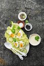 Curried egg` garden salad with lettuce, fresh cucumber slices, yogurt-based curry sauce, organic eggs with black sesame
