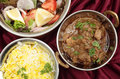 Curry and salad bowls from above indian copper dishes with homemade beef rogan josh white yellow rice a seen Stock Photo