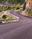 Curved mountain road narrow with a barrier surrounded by rocks and two cars visible on it in the altai mountains russia Royalty Free Stock Image