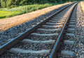 Curved railroad in sunlight single track railway tracks a rural setting Royalty Free Stock Photo