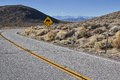 Curved road with slippery sign and distant mountains Stock Photo