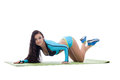 Curvy athletic brunette lying on gymnastic mat isolated white Royalty Free Stock Photo